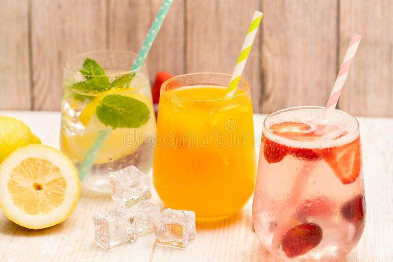 Three cold drinks strawberry, lemon water and orange juice royalty free stock images