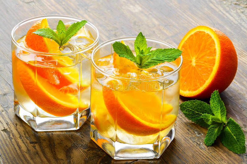 Cold drinks with ice and mint. Orange cocktail on stock photo