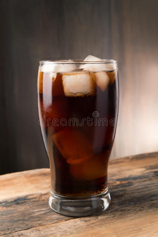Cold fizzy cola soda with ice in glass cup. Iced cola, Cold fizzy cola soda with ice in glass cup royalty free stock image