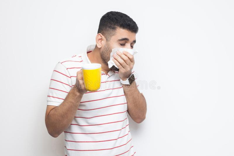 Cold and flu. Portrait of sick bearded young man in striped t-shirt standing, holding tissue, cleaning his nose, holding hot drink. Try to be treated. indoor royalty free stock photography
