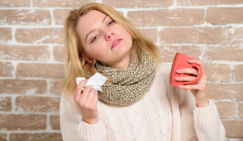 Cold and flu symptoms. Sick woman with sore throat drinking cup of warm tea. Pretty girl with nasal cold suffering from. Headache. Cute woman caught terrible royalty free stock images