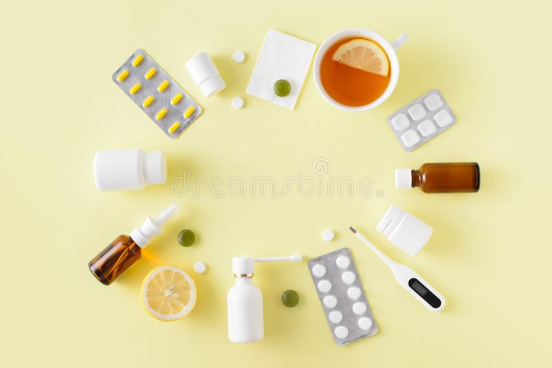 Cold and flu treatment set. Pills, throat spray, medical mask, thermometer, recipe on simple yellow background. Health care. Therapy stock photos