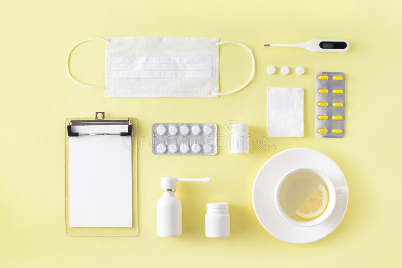 Cold and flu treatment set. Pills, throat spray, medical mask, thermometer, recipe on simple yellow background. Health care therap. Y stock images