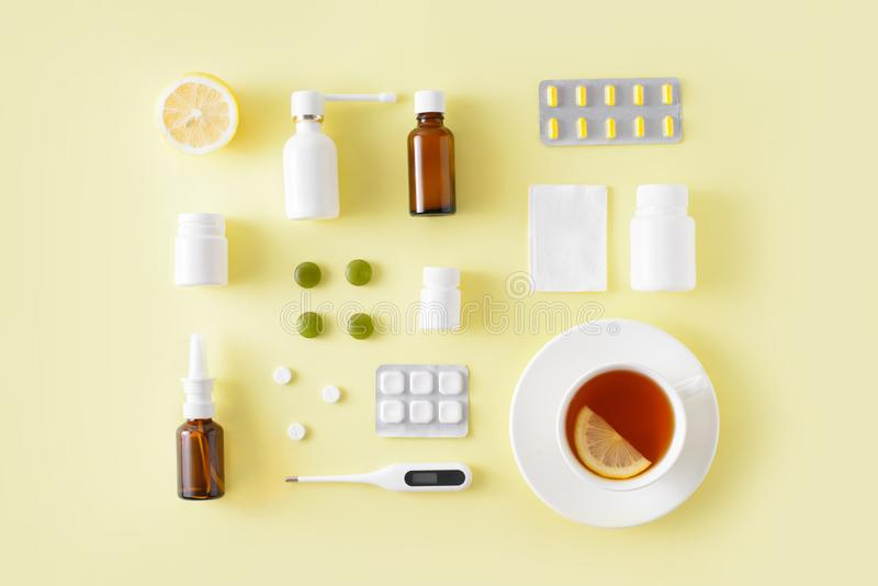 Cold and flu treatment set. Pills, throat spray, medical mask, thermometer, recipe on simple yellow background. Health care. Therapy stock image