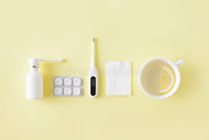 Cold and flu treatment set. Pills, throat spray, thermometer, cup of tea with lemon on simple yellow background. Health care thera royalty free stock photo