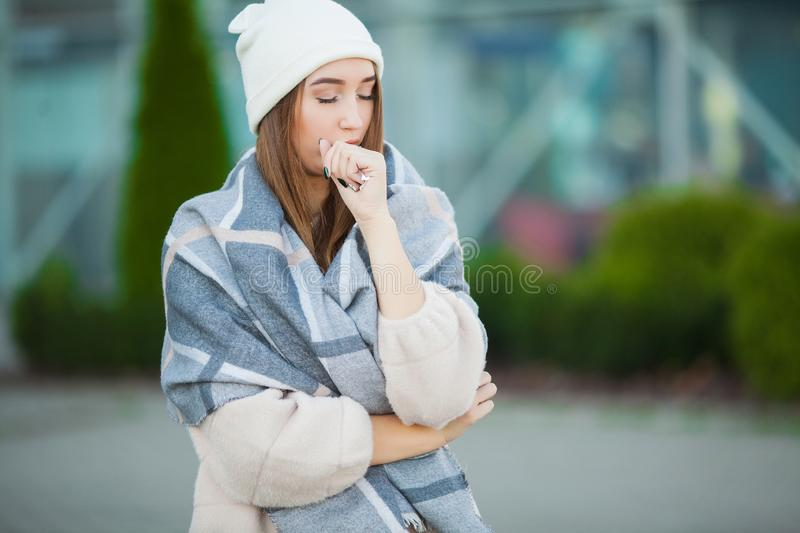 Cold and flu. Woman get sick and cough, wearing autumn clothes.  stock image