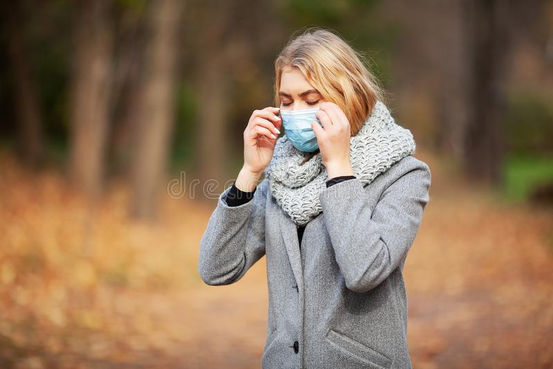 Cold and flu. Woman with a medical face mask at outdoor.  royalty free stock image