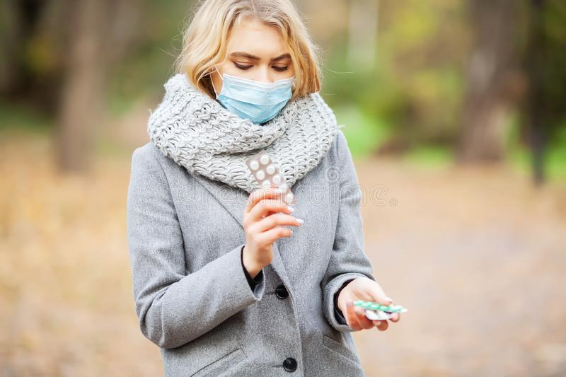 Cold and flu. Woman with a medical face mask at outdoor in autumn forest stock photo