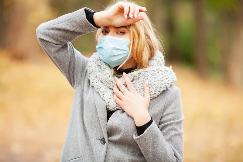 Cold and flu. Woman with a medical face mask at outdoor in autumn forest royalty free stock photos