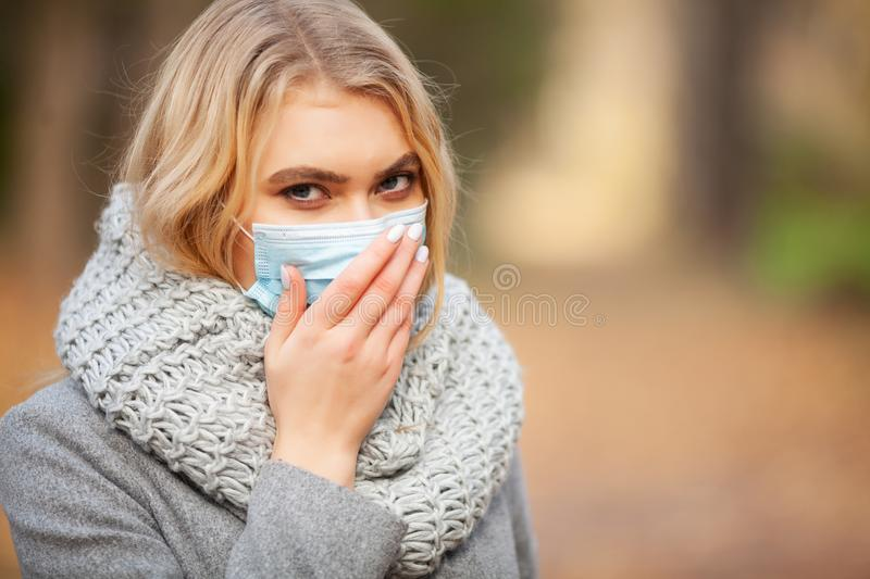 Cold and flu. Woman with a medical face mask at outdoor.  stock images