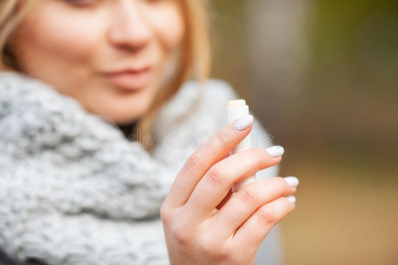 Cold and flu. Young sick woman uses a nose spray at street outside.  royalty free stock photo