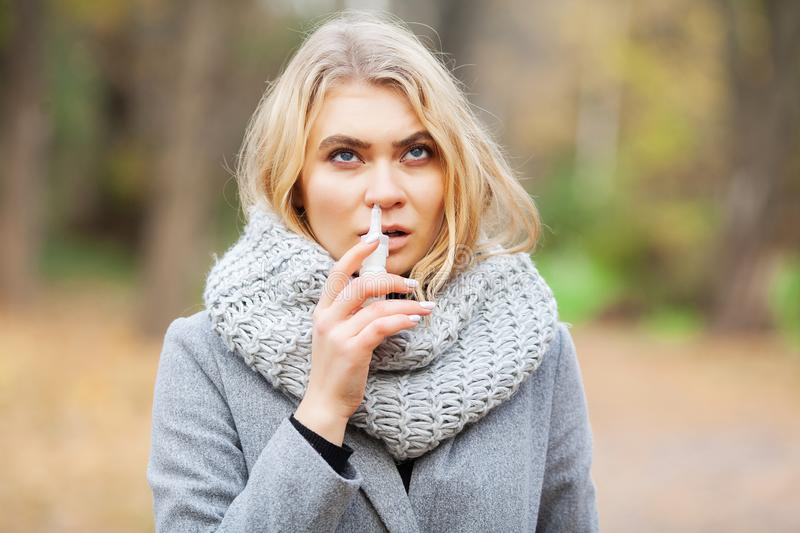 Cold and flu. Young sick woman uses a nose spray at street outside.  royalty free stock photography