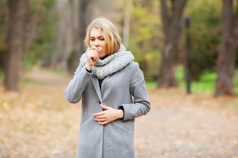 Cold and flu. Young woman in a gray coat walking in the autumn park and warms frozen hand stock images