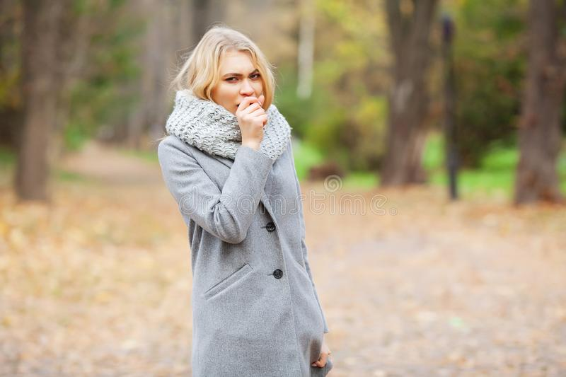 Cold and flu. Young woman in a gray coat walking in the autumn park and warms frozen hand royalty free stock images
