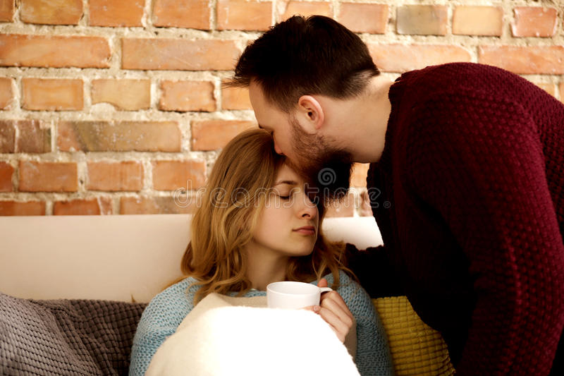 Cold or flu. Young women having cold or flu, her partner take care of her stock photos