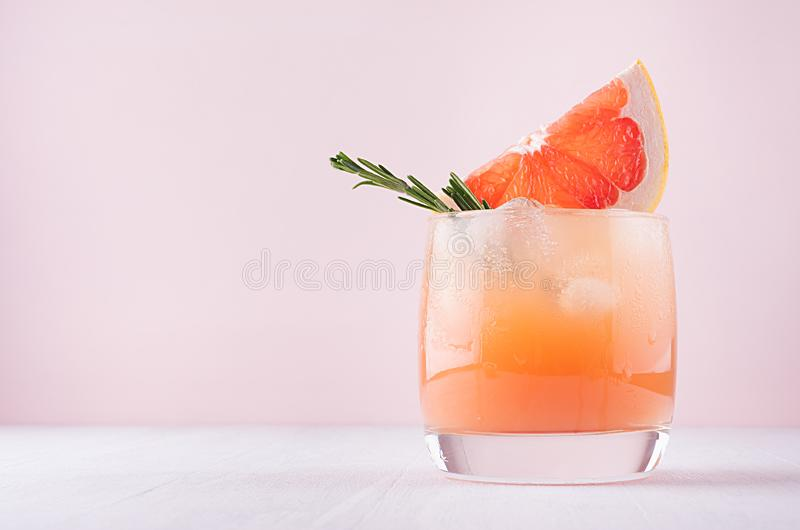 Cold fresh homemade grapefruit cocktail with ice, rosemary and pieces citrus on pastel pink background. Cold fresh homemade grapefruit cocktail with ice royalty free stock photos