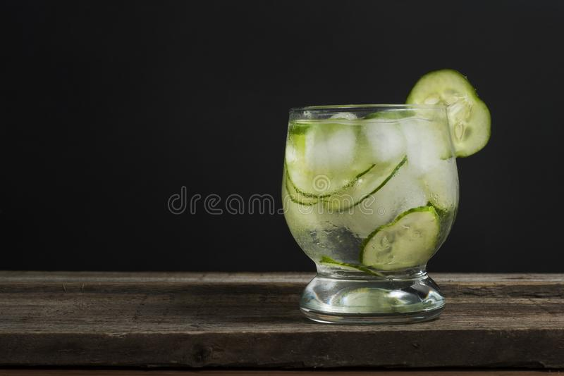 Cold fresh lemonade with cucumber, ice and mint leaves over wooden table and black background. Fresh summer drink in glass. Copy s royalty free stock photography