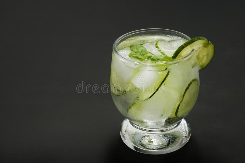 Cold fresh lemonade with cucumber, ice and mint leaves over wooden table and black background. Fresh summer drink in glass. Copy s royalty free stock images