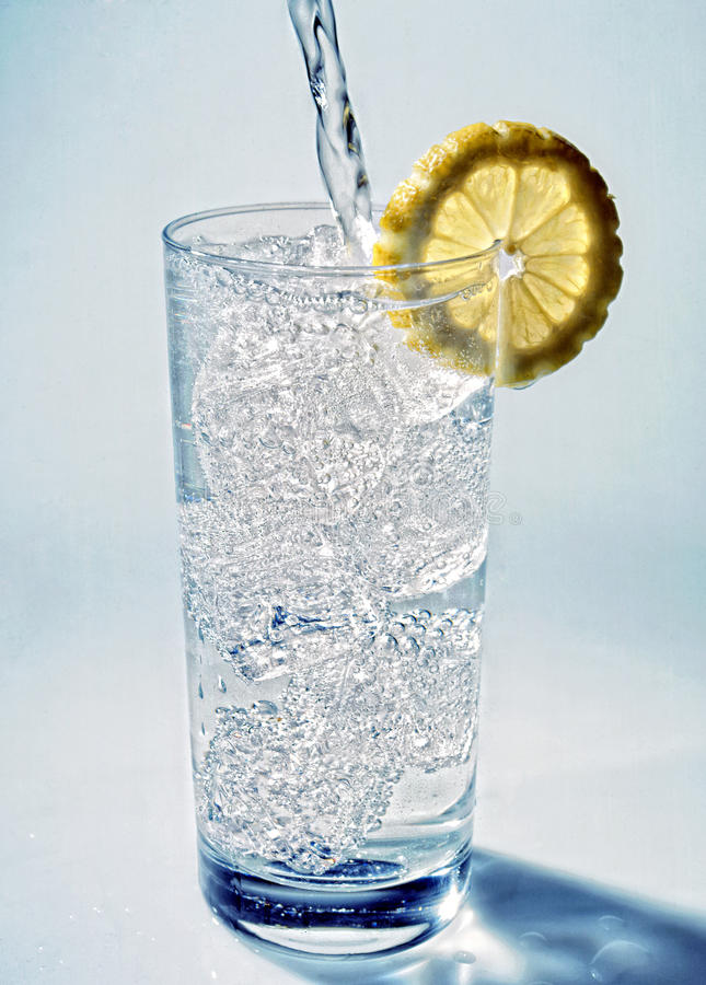 Cold fresh mineral water poured into a glass stock photography