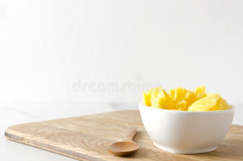 Fresh homemade ghee or clarified butter in white bowl,copy space.Healthy eating and using good products for cooking. Cold ghee in the white bowl on wooden table stock photography