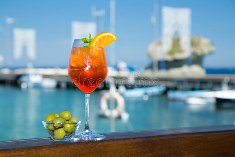 Cold glass of aperol spritz near the sea and boats. Cold glass of aperol spritz wit olives appetizer stand near the sea and boats royalty free stock image