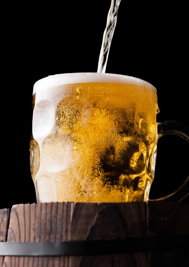 Cold glass of craft beer on old wooden barrel stock photography