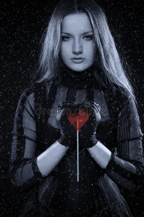 Cold gothic girl with red heart in her hands royalty free stock photo