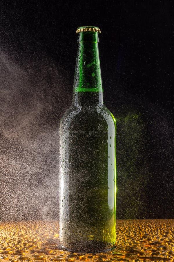 Cold green beer bottle on black stock image