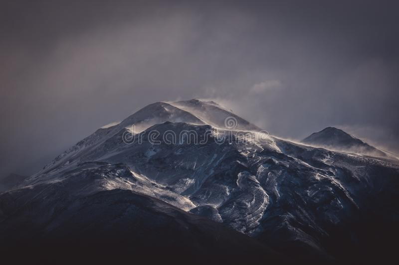 Cold grey clouds over a rugged mountain. With snow in an atmospheric winter landscape in South America royalty free stock images