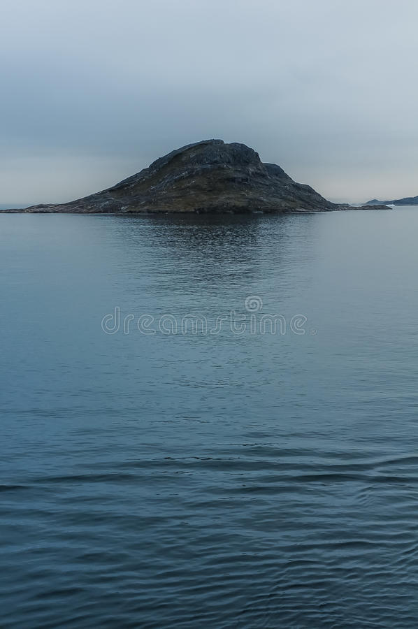 Cold hazy morning in Nanortalik, Greenland. Rocks and ocean on a cold morning during the cruise to Nanortalik, Greenland royalty free stock image