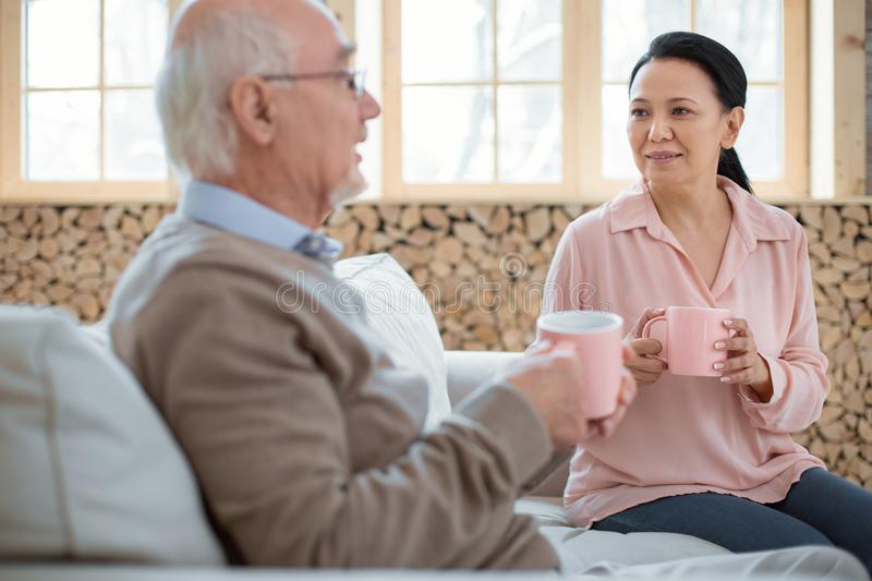 Asian caregiver encouraging senior man. Cold here. Beautiful tender caregiver and senior men chatting and sitting on couch while drinking tea royalty free stock photography