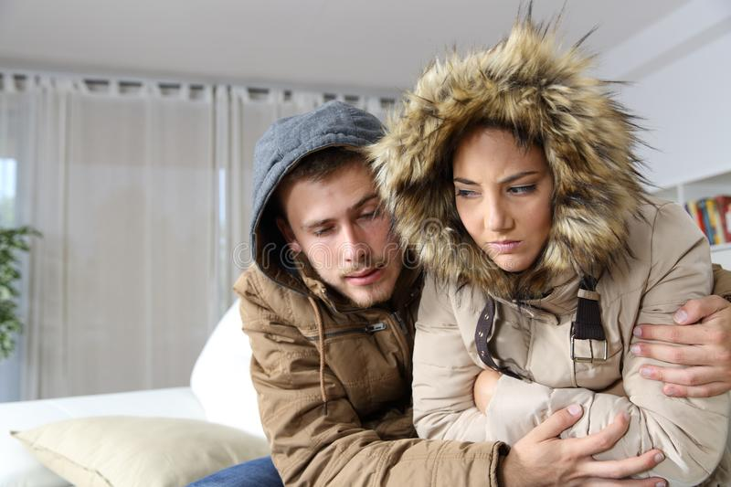 Cold home with an angry couple. Warmly clothed hugging sitting on a sofa in the living room royalty free stock photo