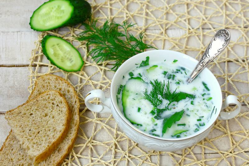 Cold kefir soup with cucumber, herbs, and garlic in white bowl stock images