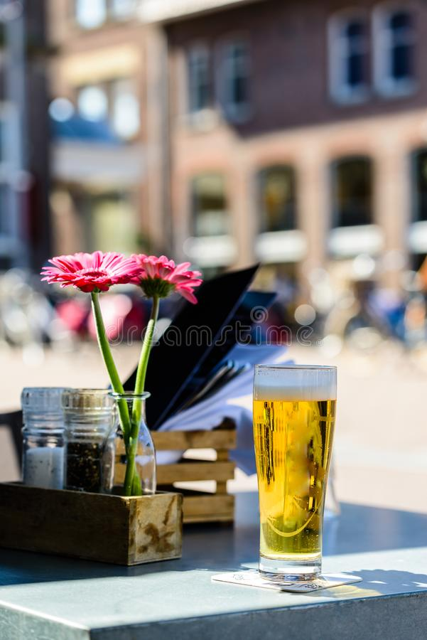 Cold light beer in the glass in street cafe stock image