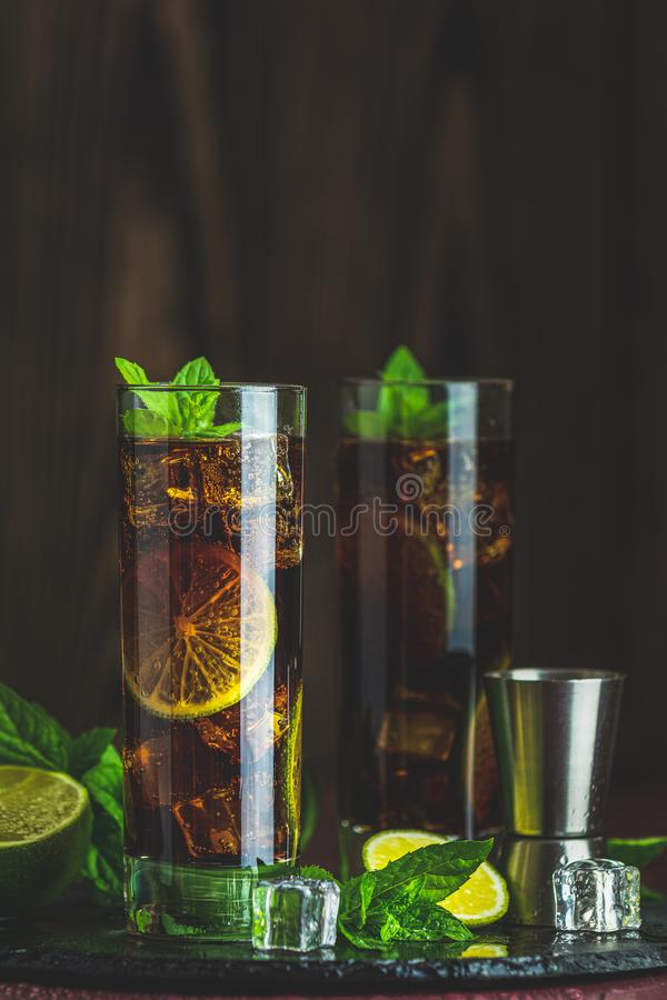 Cold Longdrink Cuba Libre with brown rum and fresh lime stock image