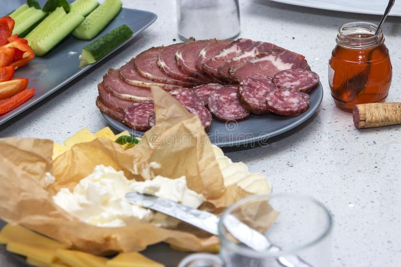 Cold meat plate Italian snacks food with ham, prosciutto, salami, pork, sausage, cheese, honey and vegetables on a table royalty free stock images