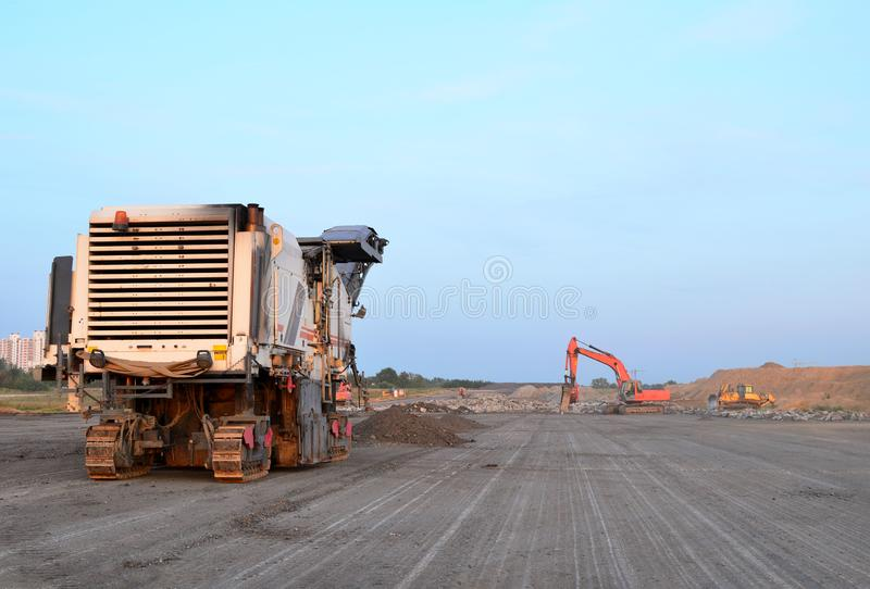 Cold milling machines are used for the quick, highly efficient removal of asphalt and concrete pavements. Removing and grinding the road surface, road royalty free stock images