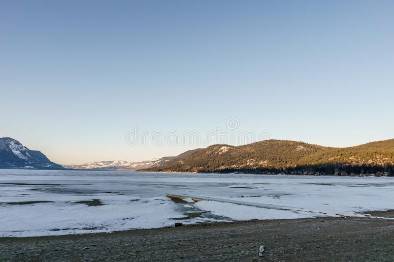 Cold morning landscape of frozen Little Shuswap Lake British Columbia Canada. Nature snow forest white winter mountain blue frost ice travel beautiful outdoors royalty free stock photography