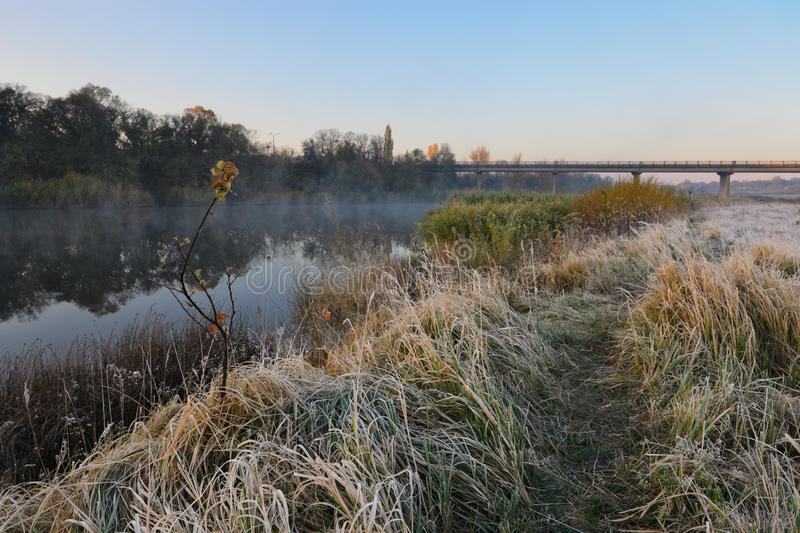 Cold morning. Landscape with a river. Grass covered by hoarfrost royalty free stock photography