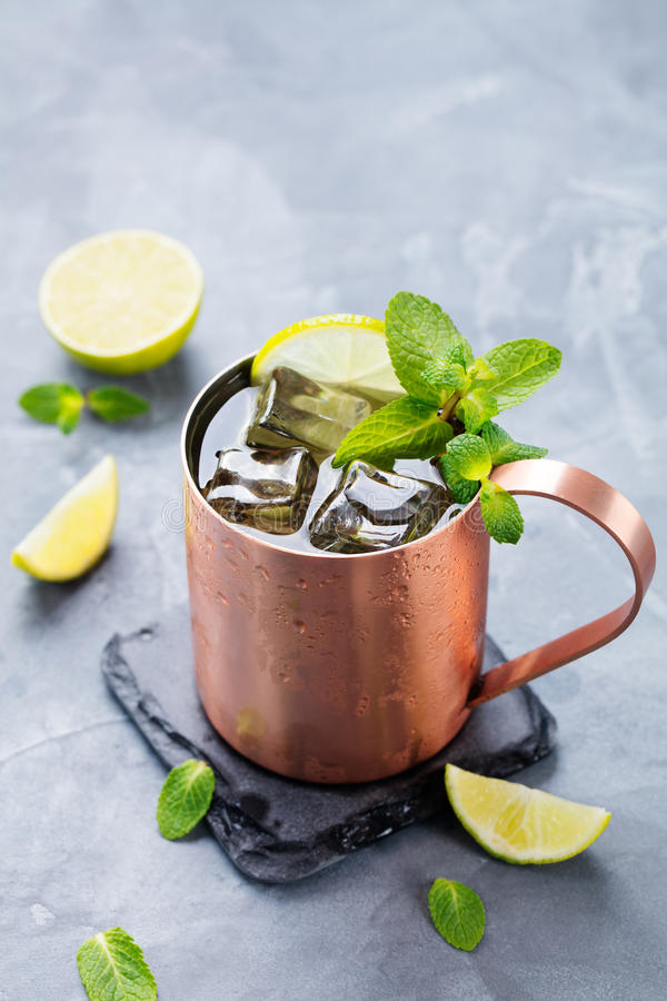 Cold Moscow Mules cocktail with ginger beer, vodka, lime. Grey stone background royalty free stock image