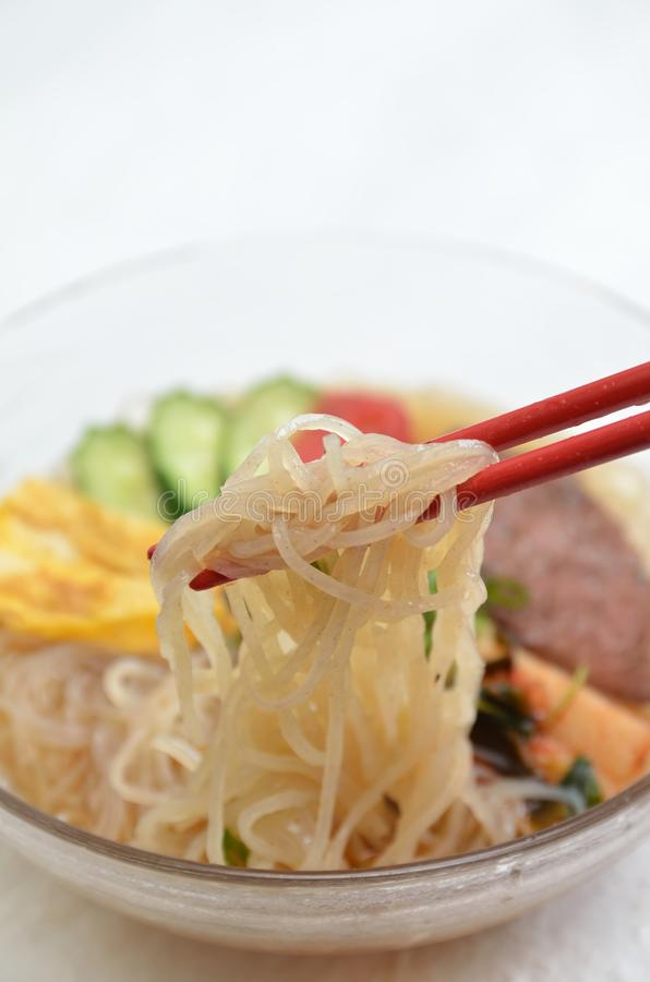 Cold noodle. (topped with egg, roast beaf, Korean pickle, tomato, and cucumber stock photo