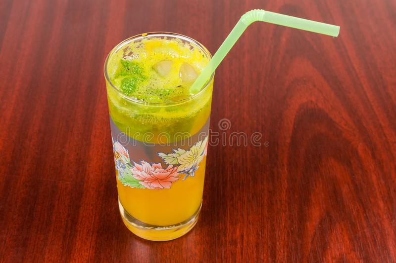 Cold orange drink in glass on a red wooden table. Prepared cold drink with freshly squeezed orange and mint in glass with drinking straw on a dark red wooden royalty free stock image