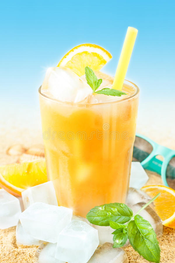 Cold orange juice with ice on beach background royalty free stock photography
