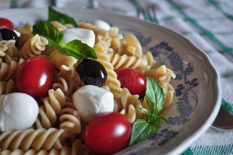 Cold pasta with mini mozzarella, cherry tomato, basil leaves, black olives and rosé wine Cerasuoloe. Cold pasta with mini mozzarella, cherry tomato, basil stock photo