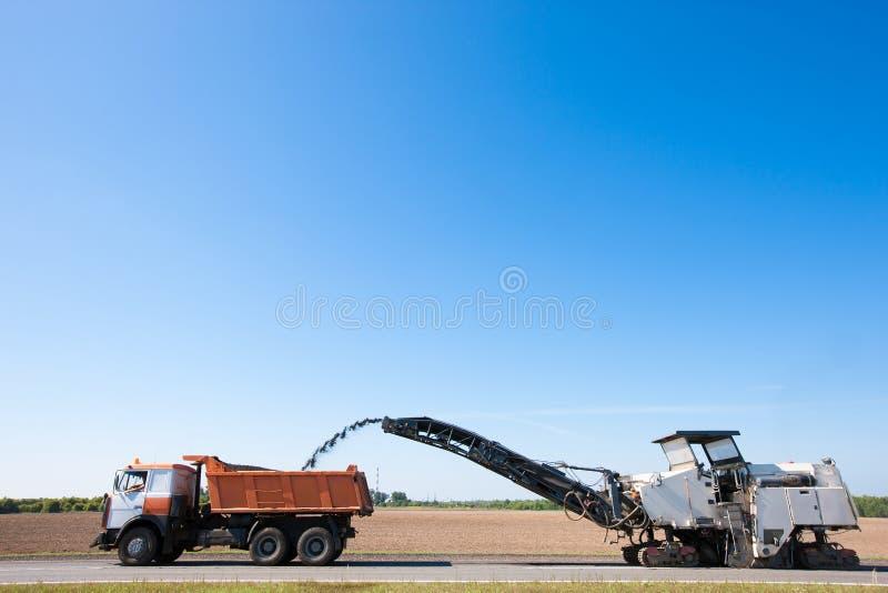 Cold planer remove worn asphalt into dumper truck stock photos