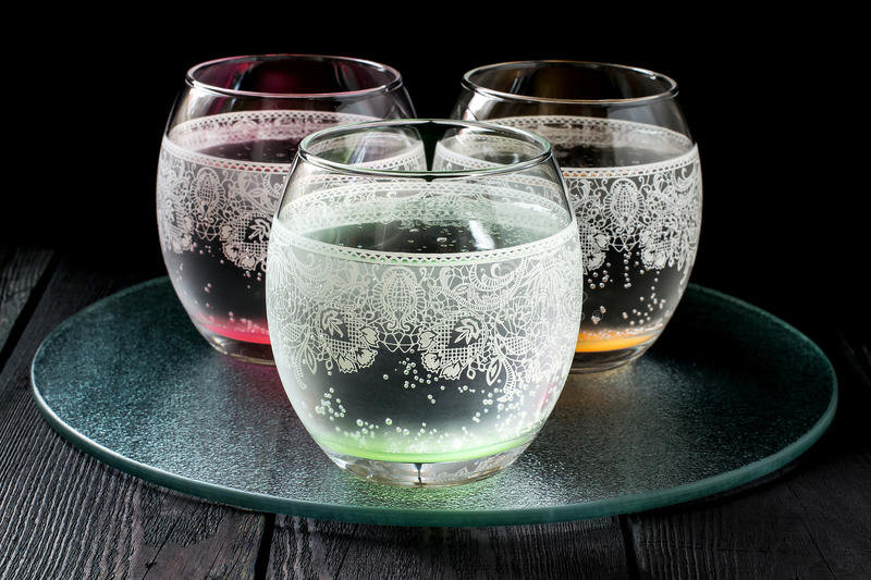Cold pure mineral water. In a beautiful glass with ornaments on the dark background royalty free stock photo