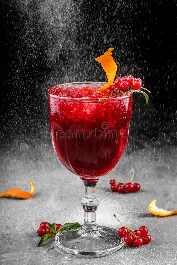 Cold red cocktail with red currant, orange and ice in tall glass on dark background. Summer drinks and alcoholic cocktails stock photo