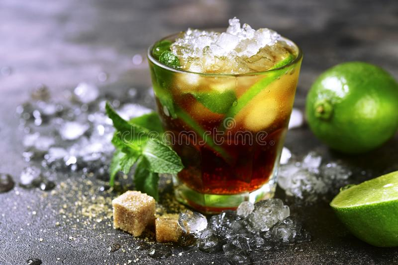Cold refreshiing summer cocktail cuba libre or iced tea with lime. Cold refreshiing summer cocktail cuba libre or iced tea with lime in a glass on a dark slate stock image
