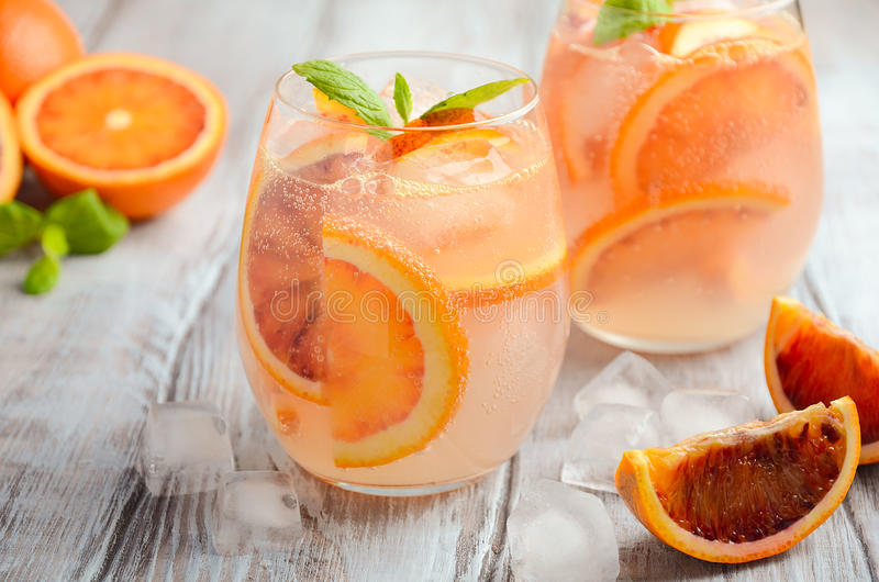 Cold refreshing drink with blood orange slices in a glass on a wooden background. royalty free stock images