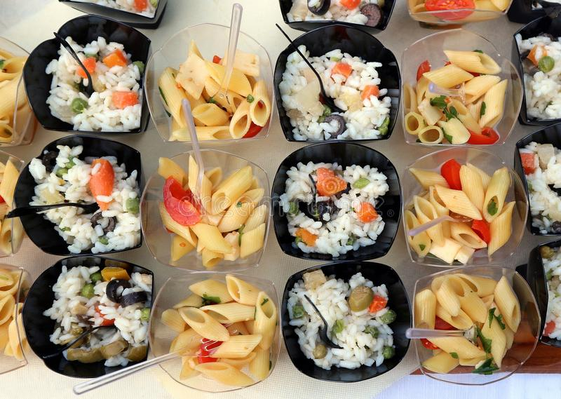 Cold rice and pasta salads in small plastic bowls, ready for a summer party stock image